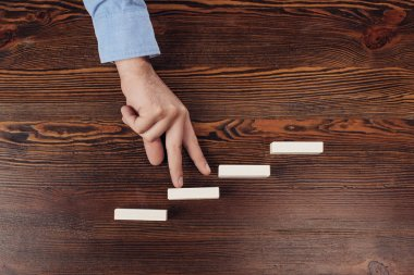 cropped view of man walking with fingers on wooden blocks symbolizing career ladder