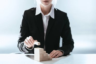 cropped view of woman putting wooden brick on top of wooden blocks symbolizing career ladder with backlit