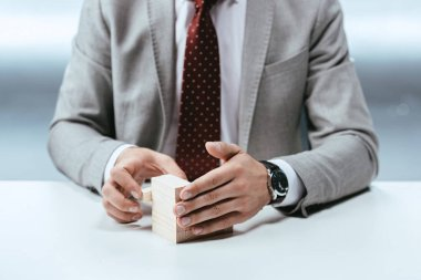 cropped view of man with wooden blocks symbolizing career ladder