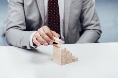 selective focus of man putting wooden brick on top of wooden blocks symbolizing career ladder