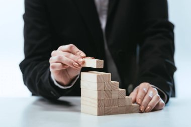 cropped view of woman putting wooden brick on top of wooden blocks symbolizing career ladder