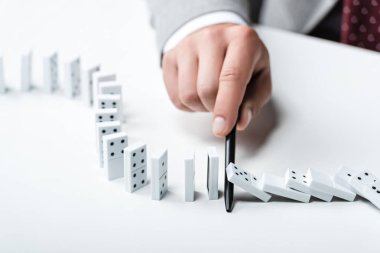 close up view of man preventing dominoes from falling with pen