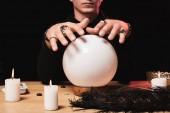 Fotografia vista potata delluomo che tengono le mani sopra la sfera di cristallo vicino a candele isolato sul nero