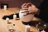 Fotografia cropped view of psychic holding hands above magical crystal ball near candles
