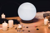 Fotografia sfera di cristallo vicino a candele e piume sulla tavola di legno isolato sul nero