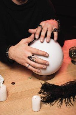 Yüzük adamla görünümünü yukarıda kristal top ahşap masa üzerinde ellerinde kırpılmış