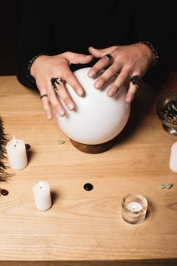 cropped view of esoteric with rings on hands above crystal ball near candles
