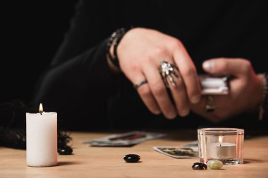 selective focus of burning candles with psychic laying tarot cards on background  isolated on black