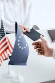 oříznutý pohled ženské cestovní kancelář poskytující služby passport k turistické poblíž americké a Evropské vlajky, izolované na bílém