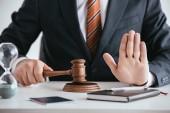 oříznutý pohled soudce v obleku drží kladívkem a zobrazeno stopku
