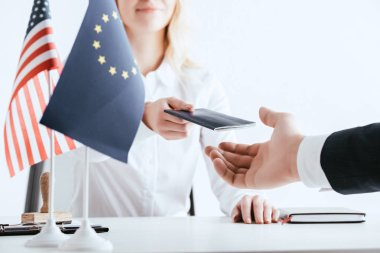 cropped view of woman giving passport to tourist near american and european flags isolated on white