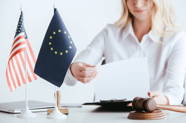 cropped view of woman holding document near american and european flags isolated on white