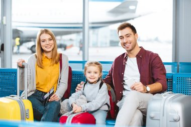 Happy family sitting in departure lounge and smiling near luggage in airport stock vector