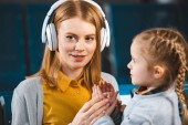 selective focus of attractive mother listening music in headphones near daughter