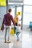 Photo mother with baggage looking at husband and daughter holding hands while meeting in airport