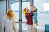 Photo selective focus of happy father holding in arms daughter near wife in airport