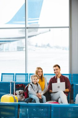 cheerful family smiling while looking at camera in departure lounge