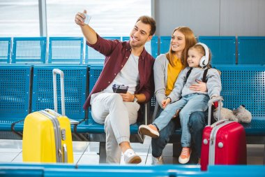 cheerful family taking selfie and smiling in airport near luggage