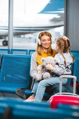 attractive mother in headphones looking at daughter with teddy bear in departure lounge