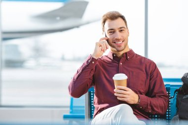 Cheerful man talking on smartphone and holding paper cup in hand in airport stock vector