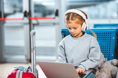 adorable child listening music in headphones and using laptop in waiting hall