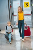 Photo attractive mother holding hands with cute daughter and walking with baggage in airport