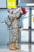 Photo happy father in military uniform holding in arms cute daughter in airport