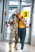 Photo happy veteran in military uniform standing with girlfriend and holding american flag in airport
