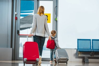 back view of mother and daughter walking with suitcases in departure lounge