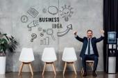 nadšený podnikatel v obleku sedí a objevovat palce v čekací hale s business idea nápis na zdi