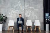 usmívající se podnikatel sedí na židli a pomocí přenosného počítače v čekací hale s sociální media ikon na zeď