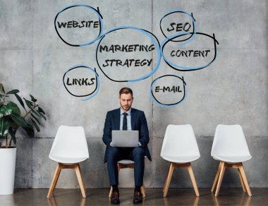smiling businessman sitting on chair and using laptop in waiting hall with marketing strategy illustration on wall