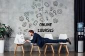 Fotografie Geschäftsmann auf Stühlen liegen und mit Laptop in Wartehalle mit Online-Kursen Schriftzug auf Wand