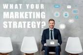 usmívající se podnikatel sedí na židli a pomocí přenosného počítače v čekací hale co vaše marketingové strategie otázkou na zdi