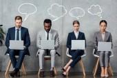 mnohonárodnostní podnikatelé sedí na židlích a používání notebooků v čekací hale s prázdné řeči a myšlení bubliny obrázek nad hlavami