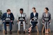 usmívající se mnohonárodnostní podnikatelé sedí na židlích a držení notebooky s obsahem, digitální, e-mail marketing a marketingové strategie nápisy na obrazovkách v čekací hale
