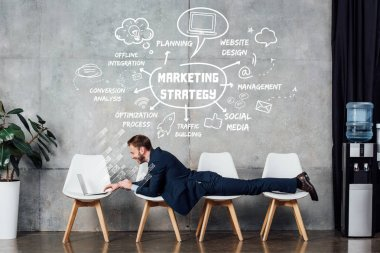 businessman lying on chairs and using laptop in waiting hall with marketing strategy illustration on wall
