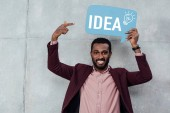 Photo smiling african american casual businessman looking at camera and pointing with finger at speech bubble with idea lettering and light bulb icon