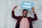 s úsměvem africké americké neformální podnikatel při pohledu na fotoaparát a ukázal prstem na bublinu s online kurzy nápisy
