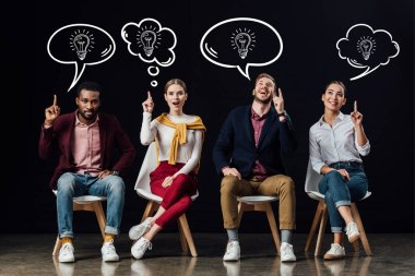 multiethnic group of people sitting on chairs and showing idea gestures with light bulbs icons in speech and thought bubbles above heads isolated on black