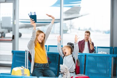 Selective focus happy mother and daughter holding hands above head and smiling in airport with man on background stock vector