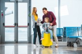 Photo cute child sitting on suitcase while mother holding teddy bear and standing near husband in departure lounge