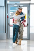 Fotografie cheerful veteran in military uniform hugging girlfriend in airport