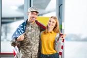 Fotografie usmívající se muž ve vojenské uniformě stojící s přítelkyní a drží Americká vlajka v Letiště