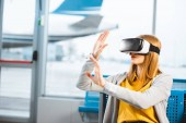 Frau trägt Virtual-Reality-Headset, während sie im Flughafen sitzt