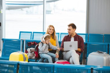 adorable daughter pointing with finger at laptop while sitting near dad and mom in airport