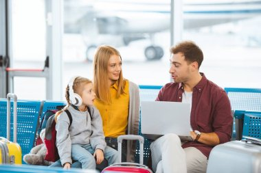 surprised kid in headphones looking at dad while sitting near mother in airport