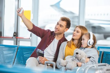 cheerful dad taking selfie and smiling near wife and daughter showing tongue in airport