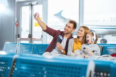 cheerful dad taking selfie and smiling with wife and daughter showing tongue in airport