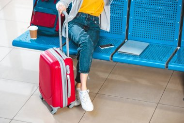cropped view of woman with luggage near backpack laptop and smartphone